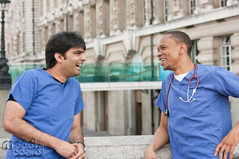 Multi ethnic doctors laughing over something with building in background