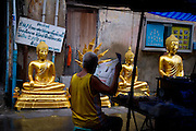 A Bangkok street vendor reads the newspaper as gold plated buddhas keep a watchful eye.
