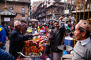 Nepali men enjoy an early morning of haggling for the best price of fresh fruits at the oldest open air market in the Thamel District in Kathmandu, Nepal.