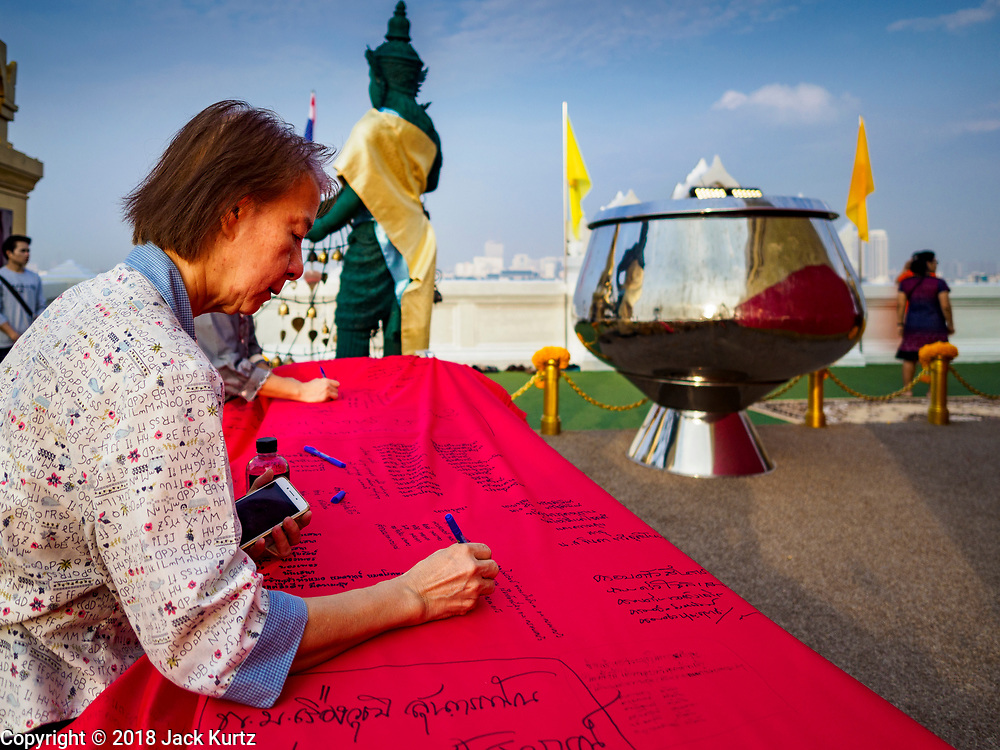 15 NOVEMBER 2018 - BANGKOK, THAILAND:  A woman writes a prayer on a red cloth that will be wrapped around the chedi at Wat Saket, also called the Golden Mount, during the red cloth ceremony. Wat Saket is on a man-made hill in the historic section of Bangkok. The temple has golden spire that is 260 feet high, which was the highest point in Bangkok for more than 100 years. The temple construction began in the 1800s during the reign of King Rama III and was completed in the reign of King Rama IV. A  red cloth (reminiscent of a monk's robe) is placed around the chedi at the top of  Golden Mount during the weeks leading up to the Thai holy day of Loy Krathong, which is November 22 this year.      PHOTO BY JACK KURTZ