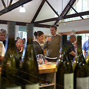 Wine tasting at the cellar door at Cloudy Bay Vineyard, Jackson Road, Marlborough, New Zealand..The winery and vineyards are situated in the Wairau Valley in Marlborough at the northern end of New Zealand's South Island. This unique and cool wine region enjoys a maritime climate with the longest hours of sunshine of any place in New Zealand. Wairau Valley, Marlborough, New Zealand. 9th February 2011. Photo Tim Clayton