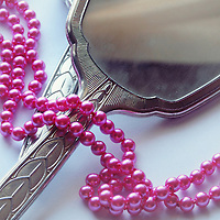 An old victorian silver mirror on a plain background, covered with a long pink pearl necklace.