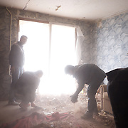 DONETSK, UKRAINE - OCTOBER 19, 2014: Local residents clean debris inside a family apartment in a residential area of central Donetsk. Shellfire from Ukrainian National Guard and the DNR rebels, fighting for the control of strategic positions around Donetsk, have in the past months indiscriminately hit residential areas in the city, claiming destruction and fatalities among the civilian population. CREDIT: Paulo Nunes dos Santos