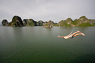 Man jumps overboard a junk, Halong Bay, Vietnam, Southeast Asia