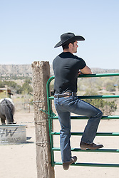 cowboy climbing on a ranch gate