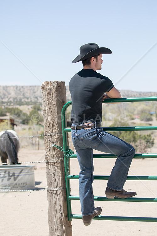 cowboy climbing on a ranch gate