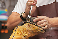 Cropped image of skilled shoemaker cutting shoe sole
