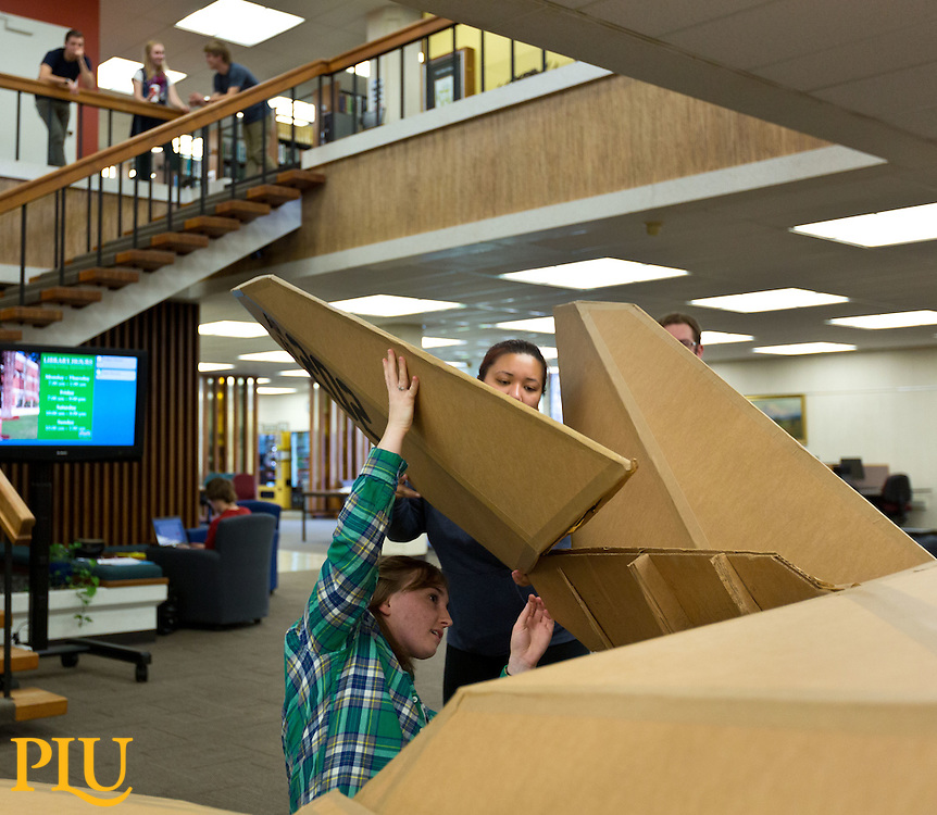 Students in Spencer Ebbinga's 3D modeling class moving a cardboard  F-117 Stealth sculpture they created in the spring of 2014 from Ingram Hall to Mortvedt Library at PLU on Thursday, Oct. 2, 2014. (PLU Photo/John Froschauer)