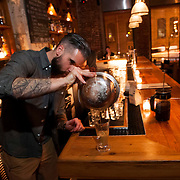 """November 18, 2013 - New York, NY : Bartender Maks Pazuniak makes his winter-warming cocktail, the """"Bitter Coffee,"""" at The Counting Room on Berry Street in Williamsburg in Brooklyn on Monday evening.  The drink is comprised of Cynar, dark rum, maple syrup, an egg yolk, vanilla, coffee, and a grating of nutmeg.  CREDIT: Karsten Moran for The New York Times"""