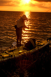 Stock photo of a man fishing beside his kayak in the bay at sunset