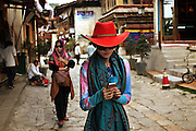 A Chinese tourist, bedecked in a new scarf and hat, walks through the streets of Dukezong, the Tibetan neighborhood of Shangri-la. The neighborhood was destroyed by fire in January, 2014.
