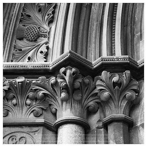 Black and white photograph of decorative masonry detail at the University of Glasgow.<br />