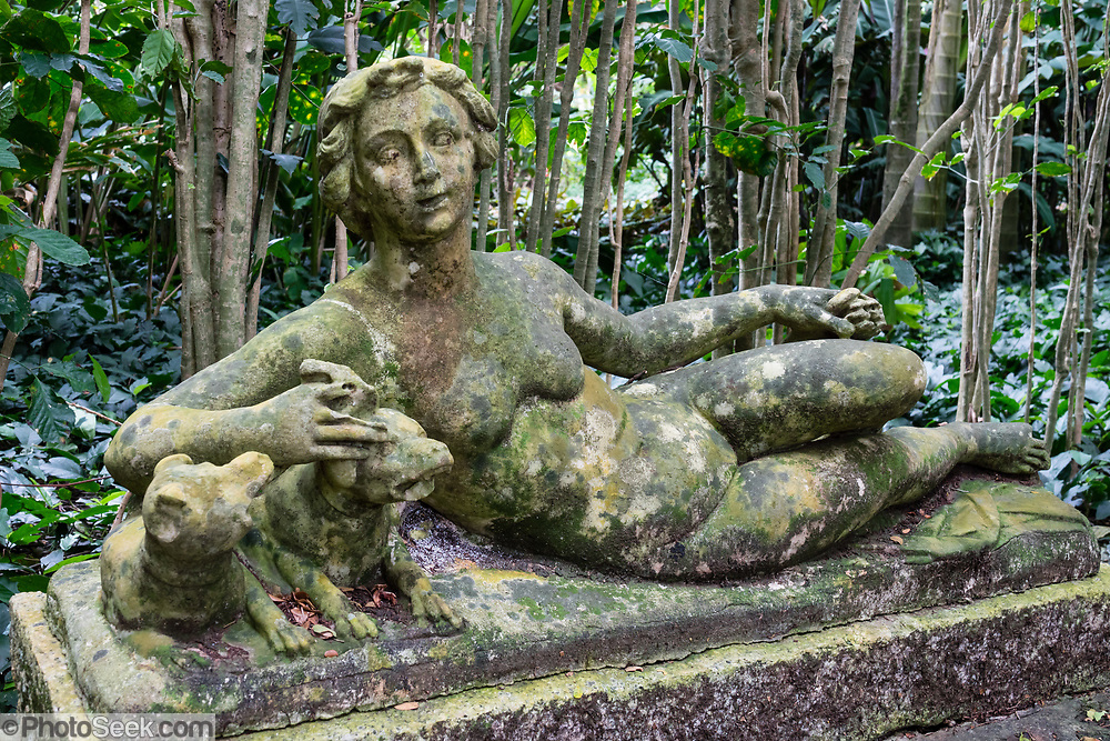 Naturally aging statue of reclining woman with two dogs at Allerton Garden, on the south shore of Kauai, Hawaii, USA. Address: 4425 Lawai Rd, Koloa, HI 96756. Nestled in a valley transected by the Lawai Stream ending in Lawai Bay, Allerton Garden is one of five gardens of the non-profit National Tropical Botanical Garden (ntbg.org).