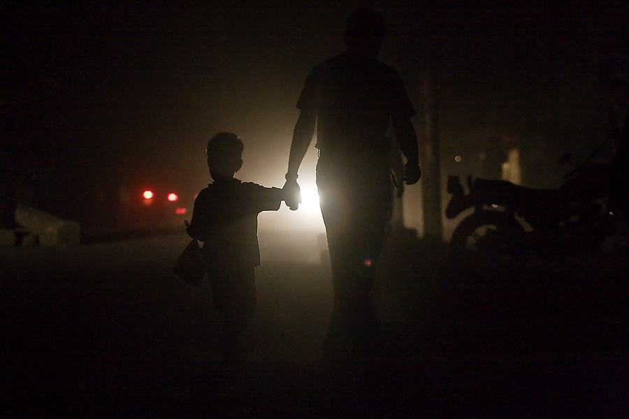 A father and son, holding hands and backlit by car headlights, walk down a dusty street at night in the dark in Boudhanath, Kathmandu, Nepal following the celebration of Buddha Jayanti (Buddha's birthday) on May 9, 2009.