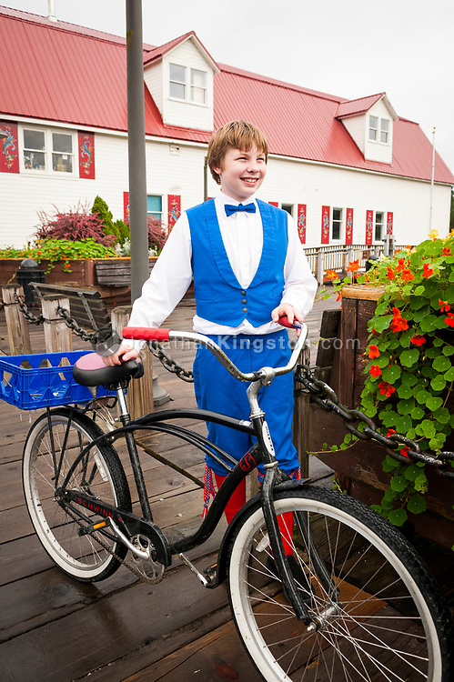 A young teenage boy wearing blue, white and red Norwegian clothing holds his bike in front of the Sons of Norway hall in Petersburg, Alaska.