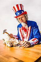 A sad and nearly crying Uncle Sam sitting over a broken piggy bank holding a hammer. Conceptual shot for treasury, deficits, bank, savings, tax revenues.