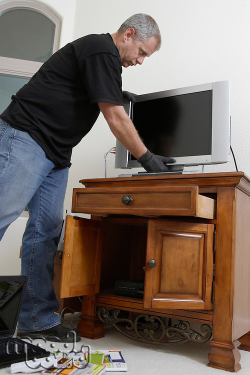 Burglar stealing television in house