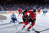 PENTICTON, CANADA - SEPTEMBER 10: Jakob Stukel #34 of Vancouver Canucks gets up after a check by Zach Fischer #48 as Dillon Dube #59 of Calgary Flames skates away with the puck on September 10, 2017 at the South Okanagan Event Centre in Penticton, British Columbia, Canada.  (Photo by Marissa Baecker/Shoot the Breeze)  *** Local Caption ***