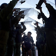 'Attitude at Altitude' Football in Potosi, Bolivia'..Peter Guerrero (Referee) is escorted from the pitch by police who use shields to protect him from missiles being thrown from the crowd during the late afternoon match between Real Potosi and Wilstermann at The Estadio Victor Agustin Ugarte, Potosi, Bolivia, Real Potosi won the match 3-0. 2nd May 2010. Photo Tim Clayton..'Attitude at Altitude' Football in Potosi, Bolivia'..The Calvario players greet the final whistle with joyous celebration, high fives and bear hugs the players are sprayed with local Potosina beer after a monumental 3-1 victory over arch rivals Galpes S.C. in the Liga Deportiva San Cristobal. The Cup Final, high in the hills over Potosi. Bolivia, is a scene familiar to many small local football leagues around the world, only this time the game isn't played on grass but a rock hard earth pitch amongst gravel and boulders and white lines that are as straight as a witches nose, The hard surface resembles the earth from Cerro Rico the huge mountain that overlooks the town. .. Sitting at 4,090M (13,420 Feet) above sea level the small mining community of Potosi, Bolivia is one of the highest cities in the world by elevation and sits 'sky high' in the hills of the land locked nation. ..Overlooking the city is the infamous mountain, Cerro Rico (rich mountain), a mountain conceived to be made of silver ore. It was the major supplier of silver for the spanish empire and has been mined since 1546, according to records 45,000 tons of pure silver were mined from Cerro Rico between 1556 and 1783, 9000 tons of which went to the Spanish Monarchy. The mountain produced fabulous wealth and became one of the largest and wealthiest cities in Latin America. The Extraordinary riches of Potosi were featured in Maguel de Cervantes famous novel 'Don Quixote'. One theory holds that the mint mark of Potosi, the letters PTSI superimposed on one another is the origin of the dollar sign...Today mainly zinc, lead, tin and small