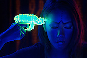 Woman points a glowing gun at her forehead.Black light