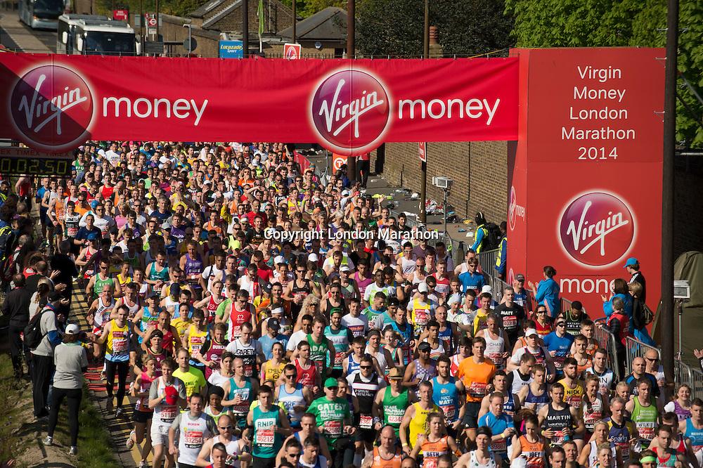 The mass of runners cross the start line at the Red Start of The Virgin Money London Marathon 2014. Sunday 13 April 2014<br /> <br /> Photo: Tom Lovelock/Virgin Money London Marathon<br /> <br /> media@london-marathon.co.ukThe Virgin Money London Marathon 2014<br /> Red Start<br /> Picture Tom Lovelock