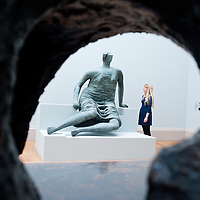 "London, UK - 13 May 2013: a Tate Employee poses for a picture next to a sculpture by Henry Moore entitled ""Draped Seated Figure 1957-8"". The new chronological presentation of the world's greatest collection of British art will allow visitors to experience the national collection of British art in a continuous chronological display from the 1500s to the present day."