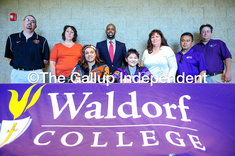 030713  Adron Gardner/Independent<br /> <br /> From left, rear, Gallup High School principal Ben Chavez,  Michelle Lovato, agent Eric Taylor Cheryl Torrez, coach Jimmy Monta&ntilde;o and Miyamura High School principal Frank Chiapetti surround Gallup Bengal, Mattea Lovato, center left, and Miyamura Patriot Corteney Torrez as they sign their letters of intent for Waldorf College at Miyamura High School Thursday.