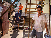 "15 FEBRUARY 2019 - SIHANOUKVILLE, CAMBODIA:  Chinese construction workers in Sihanoukville walk through their housing area on the way to lunch. The workers live in prefabbed units made in China and stacked atop each other like shipping containers. There are about 80 Chinese casinos and resort hotels open in Sihanoukville and dozens more under construction. The casinos are changing the city, once a sleepy port on Southeast Asia's ""backpacker trail"" into a booming city. The change is coming with a cost though. Many Cambodian residents of Sihanoukville  have lost their homes to make way for the casinos and the jobs are going to Chinese workers, brought in to build casinos and work in the casinos.      PHOTO BY JACK KURTZ"