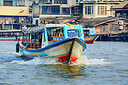 21 NOVEMBER 2012 - BANGKOK, THAILAND:  A river taxi on the Chao Phraya River in Bangkok. The boats are the fastest way to get from north to south in Bangkok. Thousands of people commute to work daily on the Chao Phraya Express Boats and fast boats that ply Khlong Saen Saeb. Boats are used to haul commodities through the city to deep water ports for export.   PHOTO BY JACK KURTZ