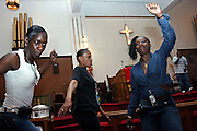 Christian devotees dancing Hip Hop music during a Mass Service at the Hip Hop Church in Harlem, New York, NY., on Thursday, July 6, 2006. A new growing phenomenon in the United States, and in particular in its most multiethnic city, New York, the Hip Hop Church is the meeting point between Hip Hop and Christianity, a place where ?God? is worshipped not according to religious dogmatisms and rules, but where the ?Holy Spirit? is celebrated by the community through young, unique, passionate Hip Hop lyrics. Its mission is to present the Christian Gospel in a setting that appeals to both, those individuals who are confessed Christians, as well as those who are not regularly attending traditional Services, while helping many youngsters from underprivileged neighbourhoods to feel part of a community, to make them feel loved and to help them not to give up when problems arise. The Hip Hop Church is not only forward-thinking but it also has an important impact where life at times can be difficult and deceiving, and where young people can be easily influenced for the worst purposes. At the Hip Hop Church, members are encouraged to sing, dance and express themselves in any way that the ?Spirit of God? moves them. Honours to students who have overcome adversity, community leaders, church leaders and some of the unsung pioneers of Hip Hop are common at this Church. Here, Hip Hop is the culture, while Jesus is the centre. Services are being mainly in Harlem, where many African Americans live; although the Hip Hop Church is not exclusive and people from any ethnic group are happily accepted and involved with as much enthusiasm. Rev. Ferguson, one of its pioneer founders, has developed ?Hip-Hop Homiletics?, a preaching and worship technique designed to reach the children in their language and highlight their sensibilities, while bringing forth Christianity. This ?Keep It Real? evangelism style is the centrepiece of Rev. Ferguson?s ministry, one that speaks the plain language of the