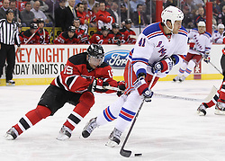 Mar 6; Newark, NJ, USA; New York Rangers defenseman Stu Bickel (41) skates with the puck while being defended by New Jersey Devils right wing Petr Sykora (15) during the second period at the Prudential Center.