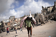 A man carrying a shark to the fishmarked in the center of the city -Death or Play. Women&acute;s Basketball in Mogadishu<br /> Women's basketball? In Europa and the U.S., we take it for granted. But consider this: In Mogadishu, war-torn capital of Somalia, young women risk their lives every time they show up to play.<br /> Suweys, the captain of the Somali women&acute;s basketball team, and her friends play the sport of the deadly enemy, called America. This is why they are on the hit list of the killer commandos of Al Shabaab, a militant islamist group, that has recently formed an alliance with the terrorist group Al Qaeda and control large swathes of Somalia.<br /> <br /> Al Shabaab, who sets bombs under market stands, blows up cinemas, and stones women, has declared the female basketball players &bdquo;un-islamic&ldquo;. One of the proposed punishments is to saw off their right hands and left feet. Or simply: shoot them.<br /> <br /> Suweys&acute; team trains behind bullet-ridden walls, in the ruins of the failed city of Mogadishu &ndash; protected by heavily armed gun-men. The women live in constant fear of the islamist killer commandos. Stop playing basketball? Never, they say.<br /> Women&acute;s basketball in the world&acute;s most dangerous capital. Female basketball in Mogadishu, Somalia.<br />