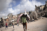 """A man carrying a shark to the fishmarked in the center of the city -Death or Play. Women´s Basketball in Mogadishu<br /> Women's basketball? In Europa and the U.S., we take it for granted. But consider this: In Mogadishu, war-torn capital of Somalia, young women risk their lives every time they show up to play.<br /> Suweys, the captain of the Somali women´s basketball team, and her friends play the sport of the deadly enemy, called America. This is why they are on the hit list of the killer commandos of Al Shabaab, a militant islamist group, that has recently formed an alliance with the terrorist group Al Qaeda and control large swathes of Somalia.<br /> <br /> Al Shabaab, who sets bombs under market stands, blows up cinemas, and stones women, has declared the female basketball players """"un-islamic"""". One of the proposed punishments is to saw off their right hands and left feet. Or simply: shoot them.<br /> <br /> Suweys´ team trains behind bullet-ridden walls, in the ruins of the failed city of Mogadishu – protected by heavily armed gun-men. The women live in constant fear of the islamist killer commandos. Stop playing basketball? Never, they say.<br /> Women´s basketball in the world´s most dangerous capital. Female basketball in Mogadishu, Somalia.<br /> A deadly game.."""