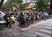 crowd of motorbikers waiting at traffic light; congestion; Hanoi; Vietnam; winter