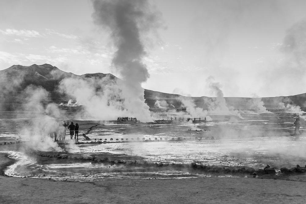 People walk between the fumaroles of the El Tatio geyser field, El Tatio, Chile.
