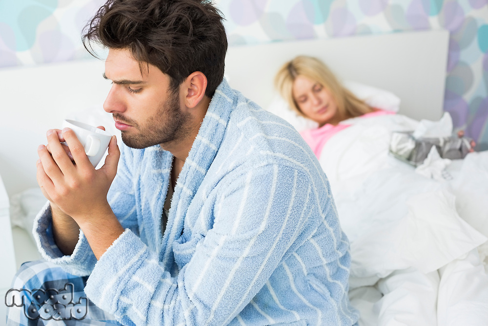 Sick man drinking coffee on bed while woman sleeping in background at home