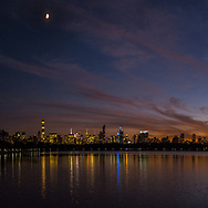 The moon over the Mid-Manhattan skyline from the Reservoir in Central Park, Sept. 26, 2017.