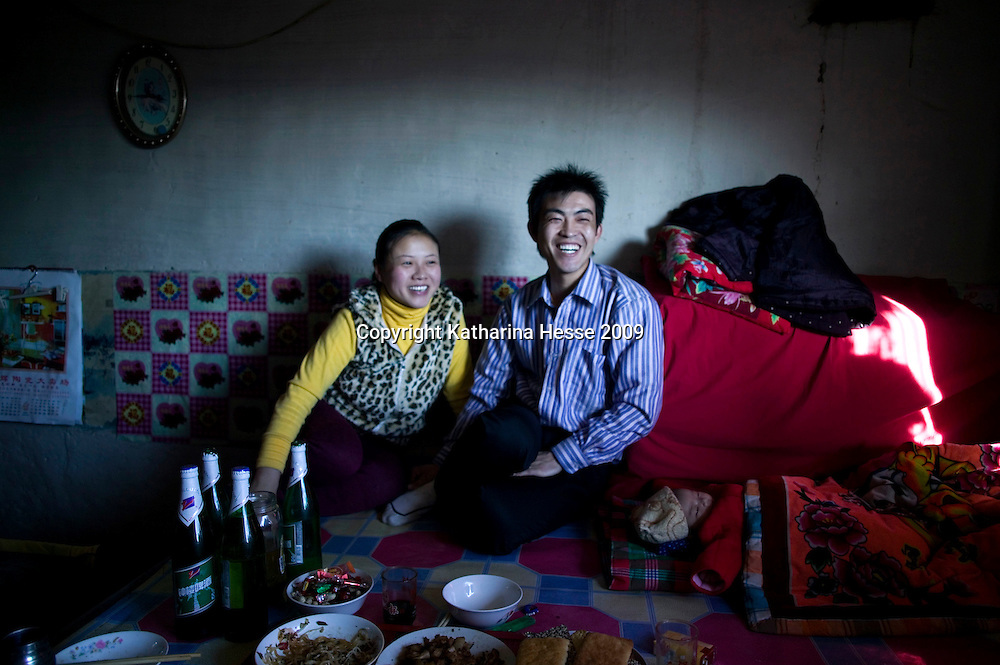 NORTHERN HEBEI PROVINCE, JANUARY 26, 2009 :<br /> Mr Lu, a textile worker in Beijing, his wife and baby relax during Chinese New Year at his parents' house in the countryside.<br /> Lu went to Beijing 8 years ago as he couldn't find a job in China's countryside.<br /> He was employed in a textile factory that went banctrupt last October. Lu and his 63 colleagues were still owed payment for 4 months, but their boss refused to pay them. They didn't know the law, nor did any of them have a contract.  <br /> At the end of January, Lu and his co-workers went to see the bosses' mother to negociate, then the union and in the end the government. They were threatened with jail . At the end of the day , a man from the union came by ( on behalf of the government )and all but an underaged worker received their due salaries.<br /> Now Lu is unemployed like 20 milion other migrant workers in China who have been laid off as a result of the financial crisis.<br /> <br /> <br /> China's Communist Party  which will celebrate its 60th anniversary in October, currently faces its biggest challenge since the beginning of the economic reforms 30 years ago  : &quot; The phase of  rapid economic growth is over. For the first time the government is threatened with a  mistrust of a wide section of the population&quot;, warns the Communist party's Shang Dewen in Beijing.   <br /> Not only the China's poorest worry about the furture, but as well China's middle class is concerned about the crisis.     1,5 Millionen university graduates didn't find a job until the end of 2008  and this summer there'll be an additional  6,1 Million new graduates. More than 12 percent of university graduates face unemployment in 2009.