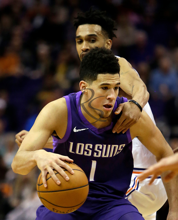 Phoenix Suns guard Devin Booker (1) gets grabbed by New York Knicks guard Courtney Lee in the second half during an NBA basketball game, Friday, Jan. 26, 2018, in Phoenix. The Knicks defeated the Suns 107-85. (AP Photo/Rick Scuteri)