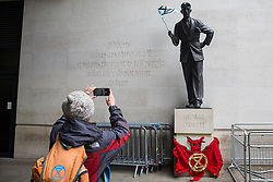 London, UK. 11 October, 2019. A climate activist from Extinction Rebellion takes a photograph of a statue of George Orwell holding an Extinction Rebellion flag outside the BBC's New Broadcasting House on the fifth day of International Rebellion protests. Activists were demanding that the broadcaster 'tell the truth' regarding the climate emergency.