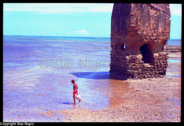 This moment was captured on an island off of the coast of Bahia,Brazil. This child fishing added a lively addition to this otherwise mysterious ruin on the beach.
