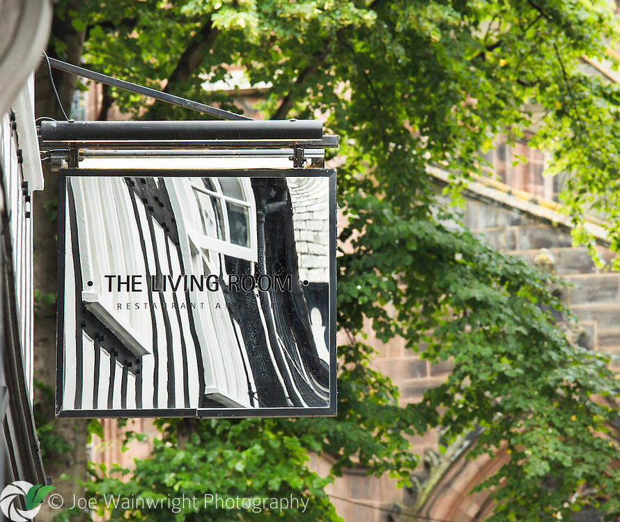 The black and white, half-timbered buildings of a Chester street are reflected in this restaurant sign.  Chester Cathedral is pictured in the background.
