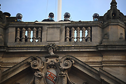 © Licensed to London News Pictures. 09/06/2020. Oxford, UK. Police officers with climbing equipment watch from the rooftop as Campaigners gather at Oriel College at Oxford University, where they are calling for the removal of a statue of controversial imperialist Cecil Rhodes. Black Lives Matter protesters recently pulled down a statue of slave trader Edward Colston in Bristol town centre, following the death of George Floyd in the U. S. A . Photo credit: Ben Cawthra/LNP