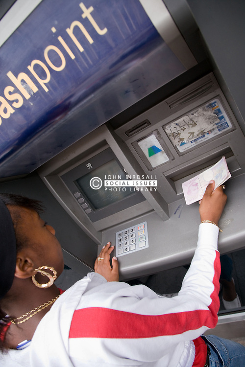 Teenage girl withdrawing cash from an ATM,
