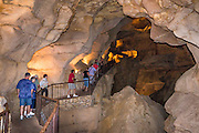 "People explore pathways in Caverns of Sonora, Sutton County, Texas, USA. The world-class Caverns of Sonora have a stunning and sparkling array of speleothems (helictites, stalactites, stalagmites, flowstone, coral trees, and other calcite crystal formations). National Speleological Society co-founder, Bill Stephenson said, after seeing it for the first time, ""The beauty of Caverns of Sonora cannot be exaggerated...not even by a Texan!"" Geologically, the cave formed between 1.5 to 5 million years ago within 100-million-year-old (Cretaceous) Segovia limestone, of the Edward limestone group. A fault allowed gases to rise up to mix with aquifer water, making acid which dissolved the limestone, leaving the cave. Between 1 and 3 million years ago, the water drained from the cave, after which speleothems begain forming. It is one of the most active caves in the world, with over 95% of its formations still growing. Sonora Caves are on Interstate 10, about half-way between Big Bend National Park and San Antonio, Texas."