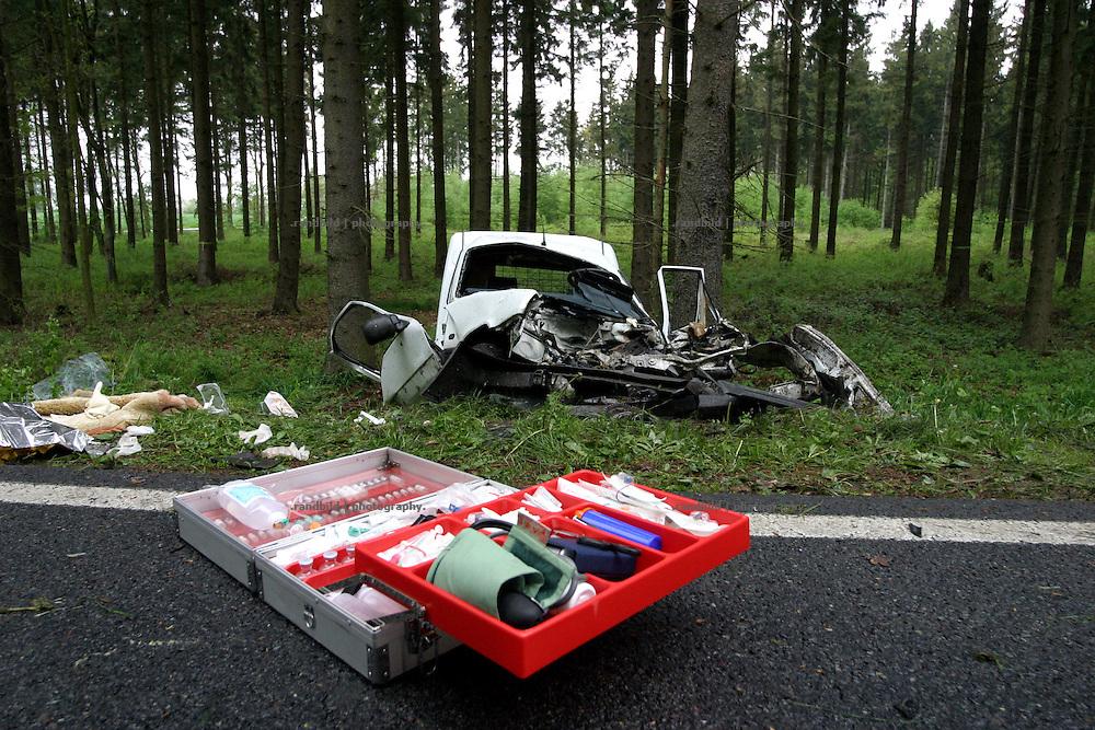Nach der Behandlung eines Schwerverletzten, steht noch ein Notarztkoffer auf der Strasse. Der verunglückte PKW liegt völlig zerstört am Waldrand. An car accident on a german national road.