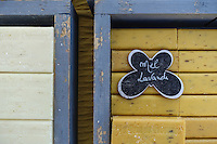 Yellow and white bars of French lavender soap displayed in weathered  periwinkle wooden boxes. Lettering on a butterfly shaped sign on the cakes of soap translates as honey lavender