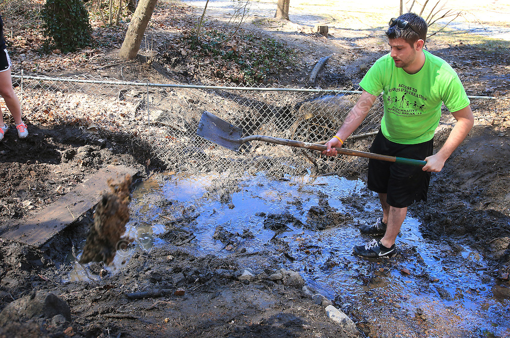 Scott Thrun, of Haslett, volunteers works at clearing a stream bed and firming up it's banks. He was among nine CMU students on their Alternative Break who arrived at the YMCA of Western NC Youth Service Center to spend the week to help with projects to improve the center and in the community. They addressed access to sports and recreation and built a kiosk, cleared a stream bed and worked with elementary students in an after school program as their Alternative Break project. CMU is ranked fourth in the nation for the number of students participating in Alternative Breaks and fifth in the country for the most trips coordinated by a university. The program organizes about 40 trips each year with more than 400 students participating. Photo by Steve Jessmore/Central Michigan University
