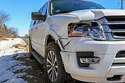 White SUV shows damage from impact with deer on a rural roadway.
