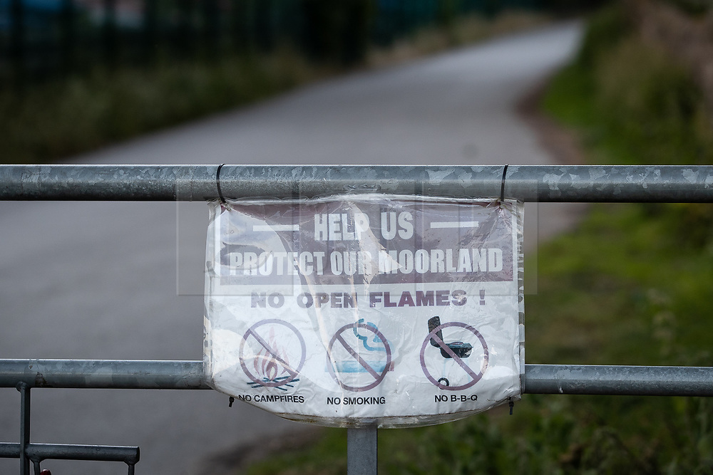 """© Licensed to London News Pictures . 28/06/2018 . Saddleworth , UK . Warnings of a high fire risk posted on gates around Dove Stone reservoir as the army are being called in to support fire-fighters , who continue to work to contain large wildfires spreading across Saddleworth Moor and affecting people across Manchester and surrounding towns . Very high temperatures , winds and dry peat are hampering efforts to contain the fire , described as """" unprecedented """" by police and reported to be the largest in living memory . Photo credit: Joel Goodman/LNP"""